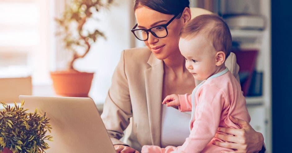 madre trabajando con su bebé frente a una computadora
