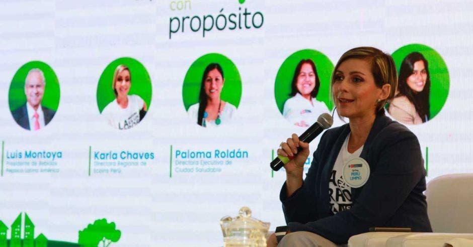 Una mujer con un microfono se dirige a un publico