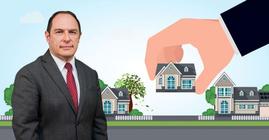 Un hombre de mediana edad posa junto a una casa