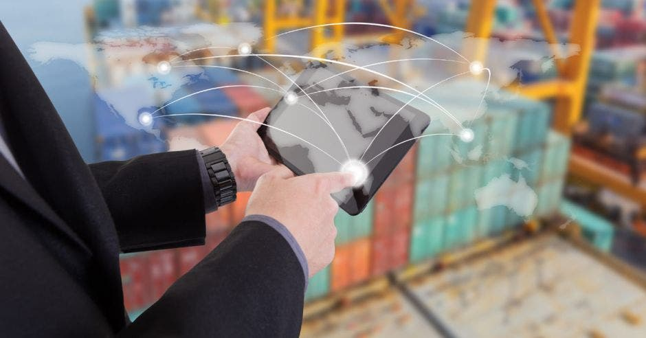 persona con una tableta en la  mano y conteneddores de fondo