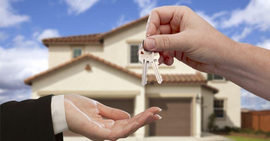 persona dandole las llaves a otra, una casa al fondo
