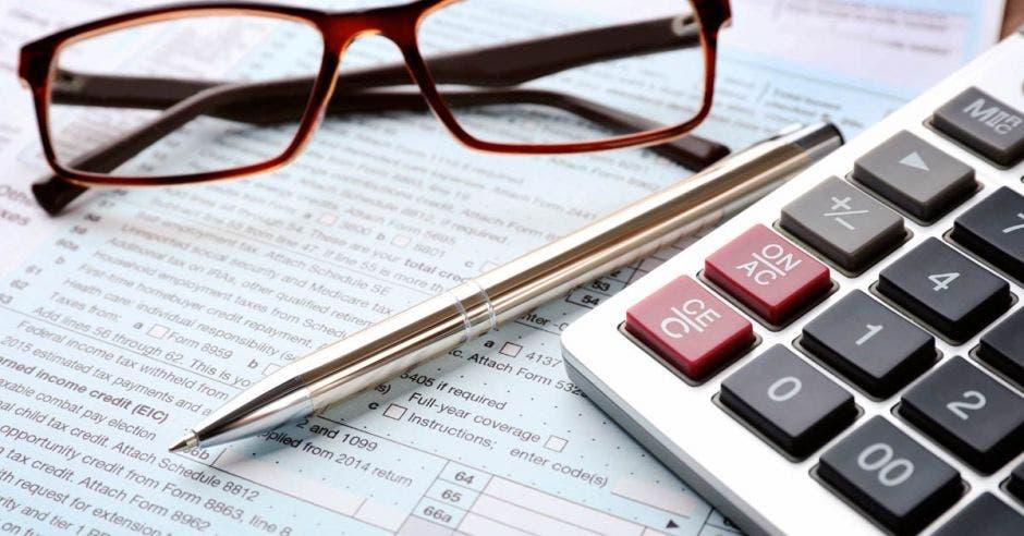 Calculadora lentes y lapiceero sobre libro con numeros