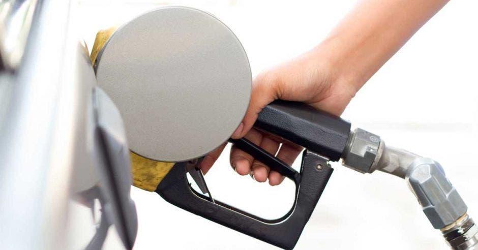 Una pistola echando gasolina en un tanque de gasolina de un carro blanco