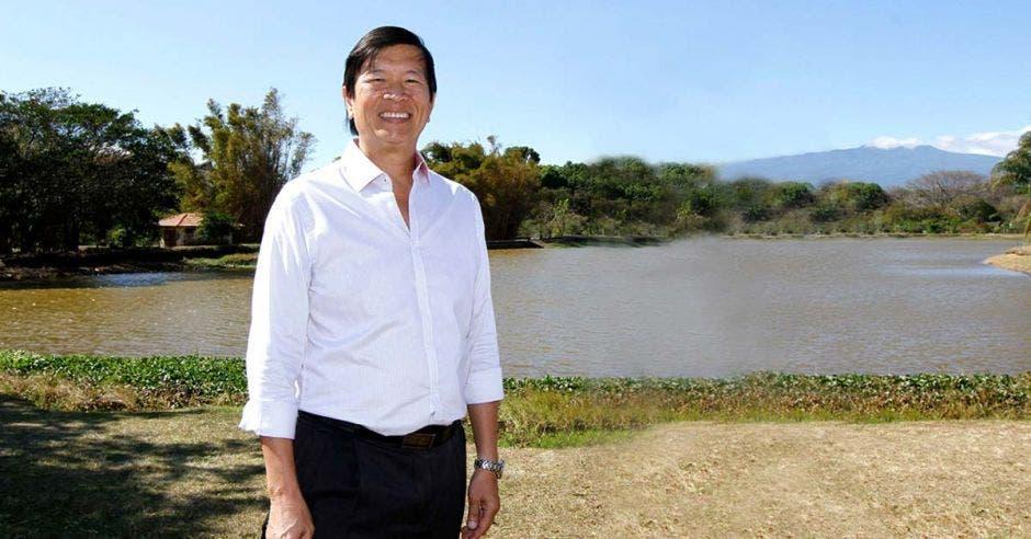 Un adulto asiático viste camisa blanca y pantalones, con el lago de la sabana de fondo