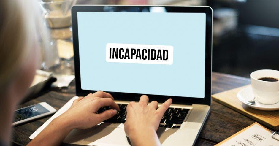 Una computadora y unas manos con la palabra incapacidad