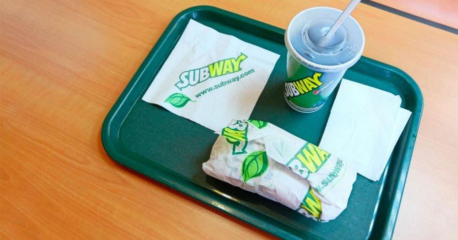 Una bandeja de subway con un vaso de gaseosa y un sándwich