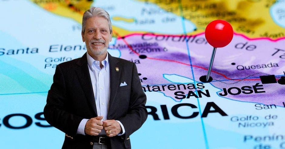 Un señor de barba y bigote blancos con traje oscuro posa sobre un mapa de Costa Rica