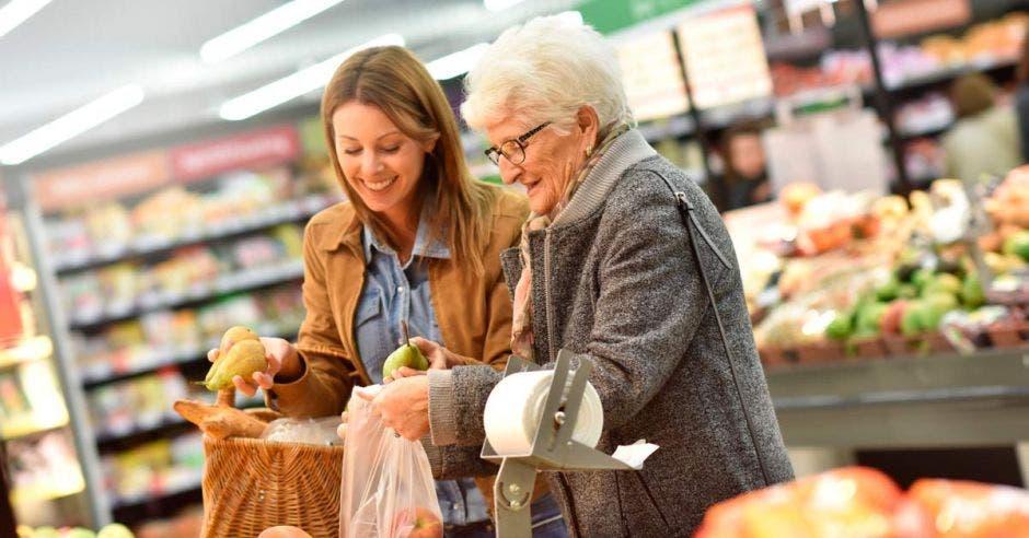Una mujer joven ayuda a una adulta mayor a hacer sus compras