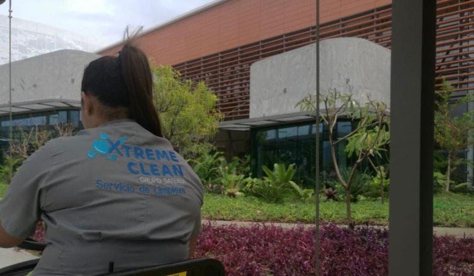 Una mujer limpiando con una camisa de Xtreme Clean, en una mesa de afuera de un edificio