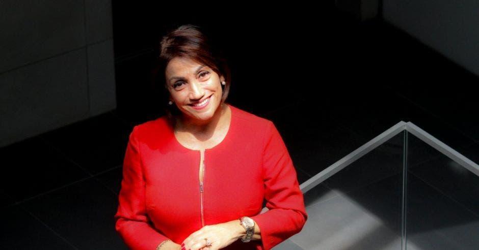 Una mujer con un traje rojo apoyada sobre una escalera