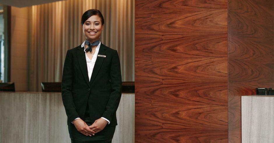 Una mujer de piel oscura posa en el lobby de un hotel