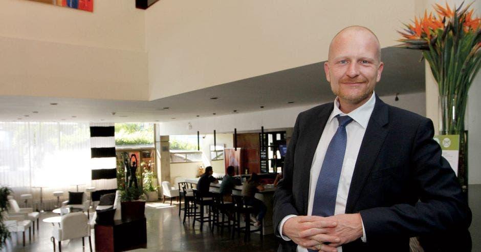 Un señor calvo sonríe en el lobby de un hotel