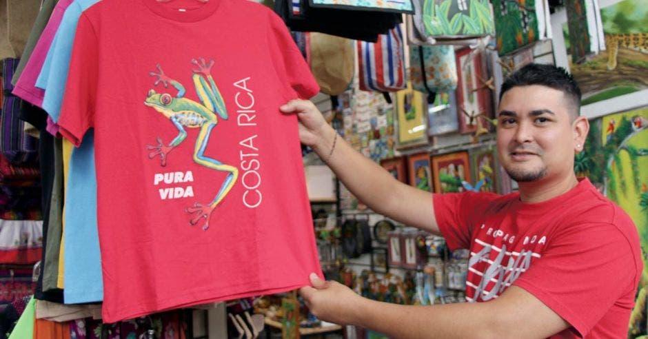 Un muchacho con camisa roja muestra una camisa
