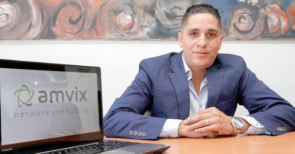 El director de Amvix, con traje entero en un escritorio y la computadora a un lado con el logo de la empresa Amvix
