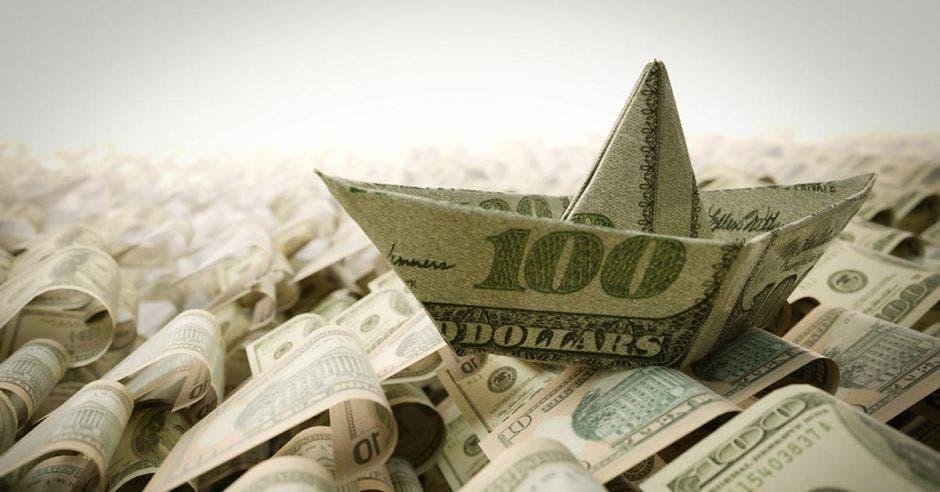 barcos de papel pero hechos con dólares en un mar de dólares