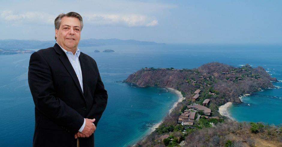 Un señor de avanzada edad posa frente un golfo de mar cristalino