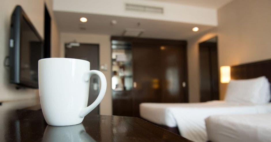 Una taza sobre una repisa en una habitación de hotel