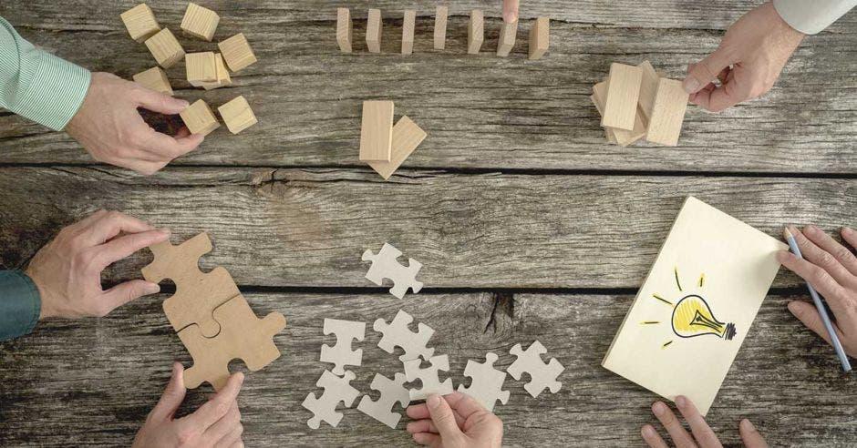 piezas de rompecabezas cubos y hoja con dibujo de bombillo