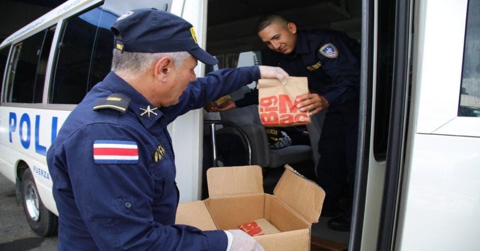 Oficiales de la fuerza pública recibiendo paquete de comida de McDonald's