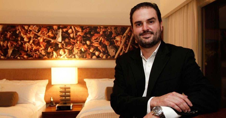 Un hombre adulto con barba sonríe en una habitación de hotel