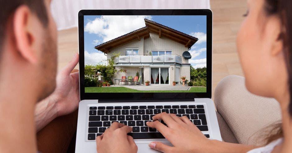 pareja viendo una casa en computadora