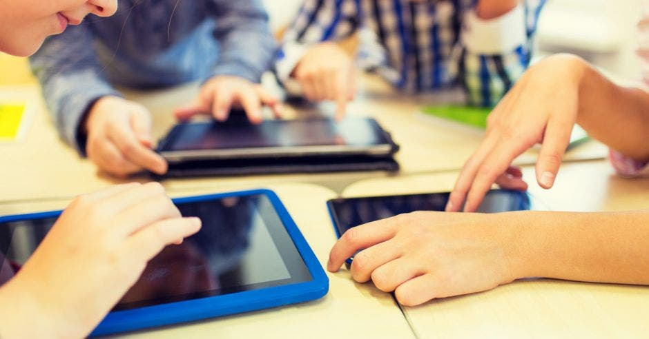 Niños manipulando tabletas