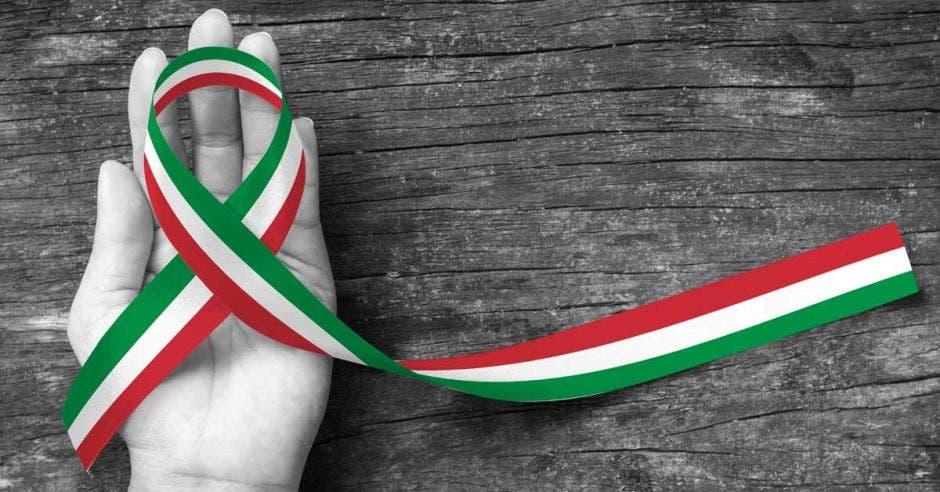 Una mano sostiene un lazo con los colores de la bandera italiana