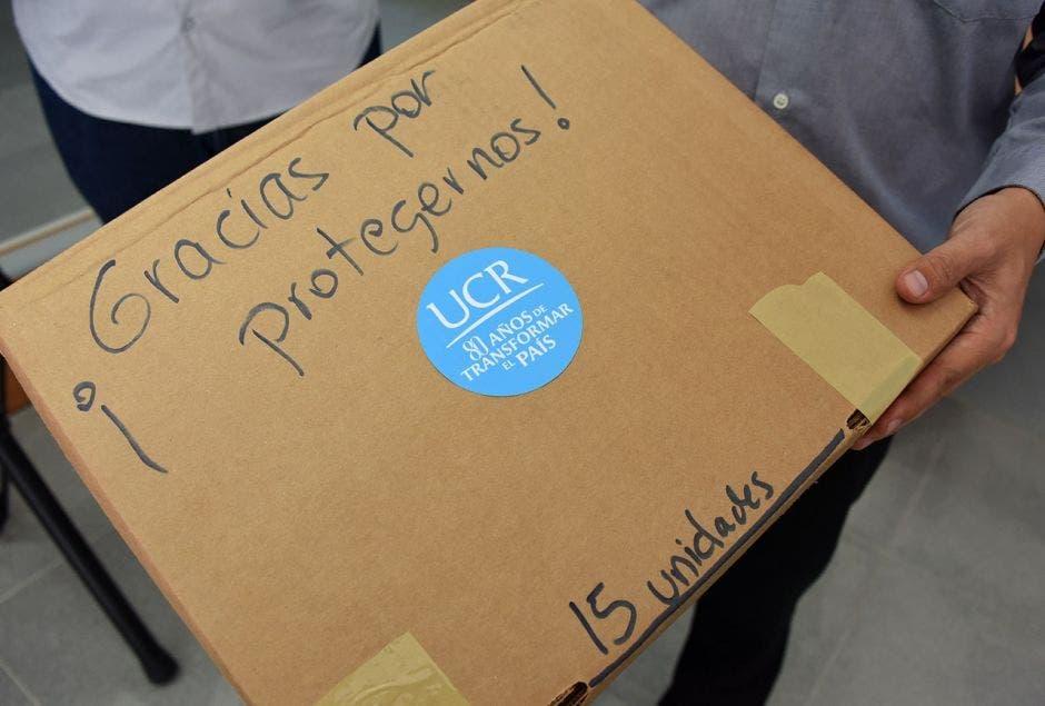 Una caja de protectores faciales con el logo de la UCR