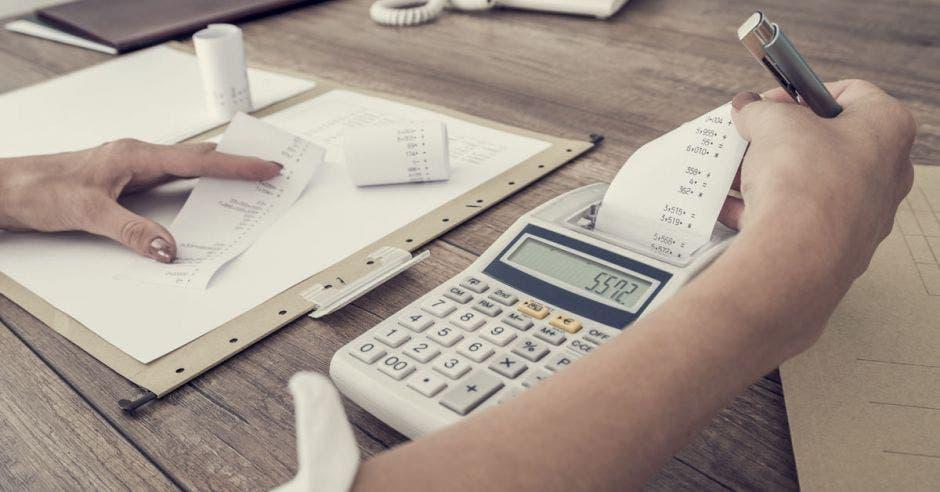 Persona con una calculadora  y un libro  sacando  cálculos