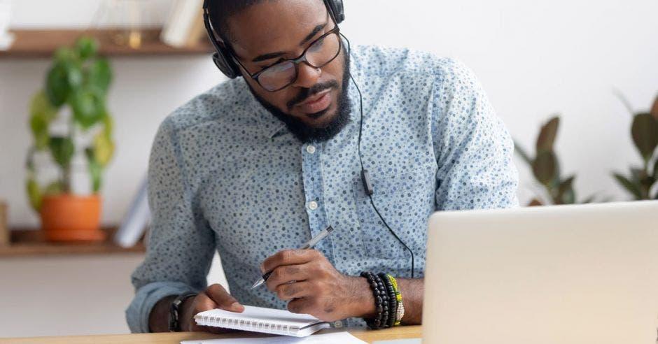 Un hombre de tez negra utiliza una computadora mientras realiza apuntes