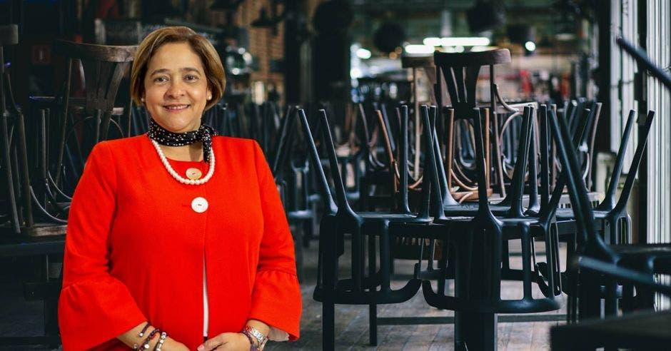 Una señora con traje rojo sobre un fondo de sillas puestas sobre mesas