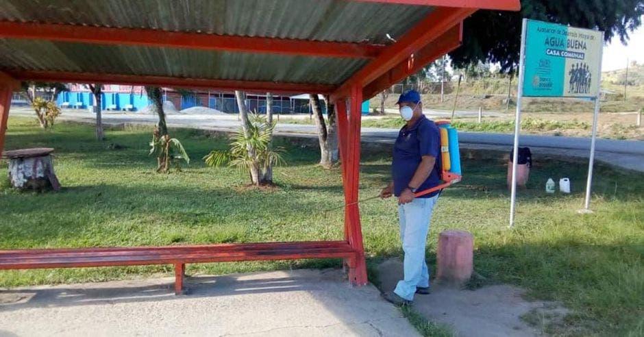 Colaborador municipal desinfectando una parada de bus