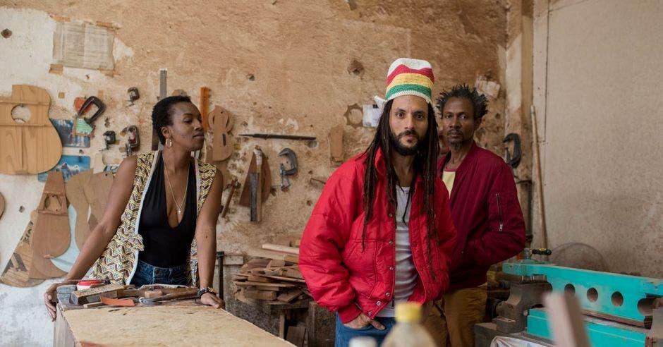 Una de las vocalistas junto al bajista y el vocalista en una taller de carpintería