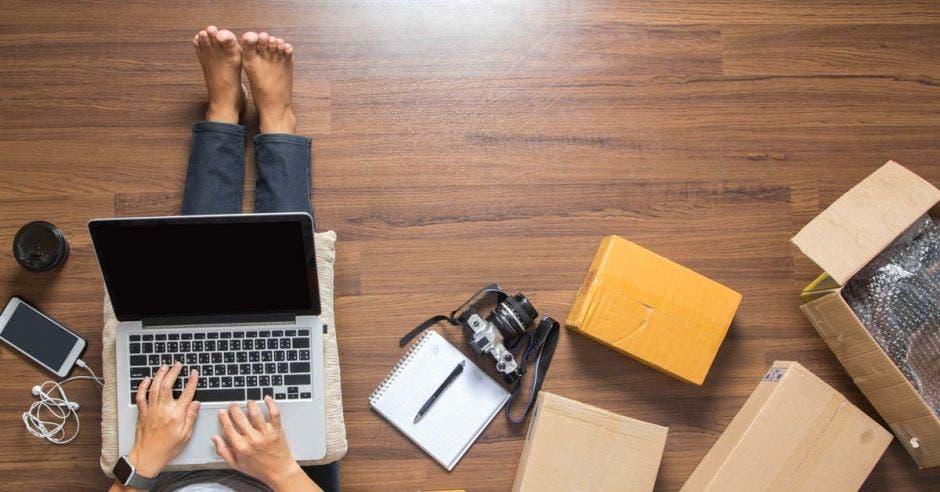 Una mujer sentada en el suelo consulta en su computadora detalles sobre comercio electrónico