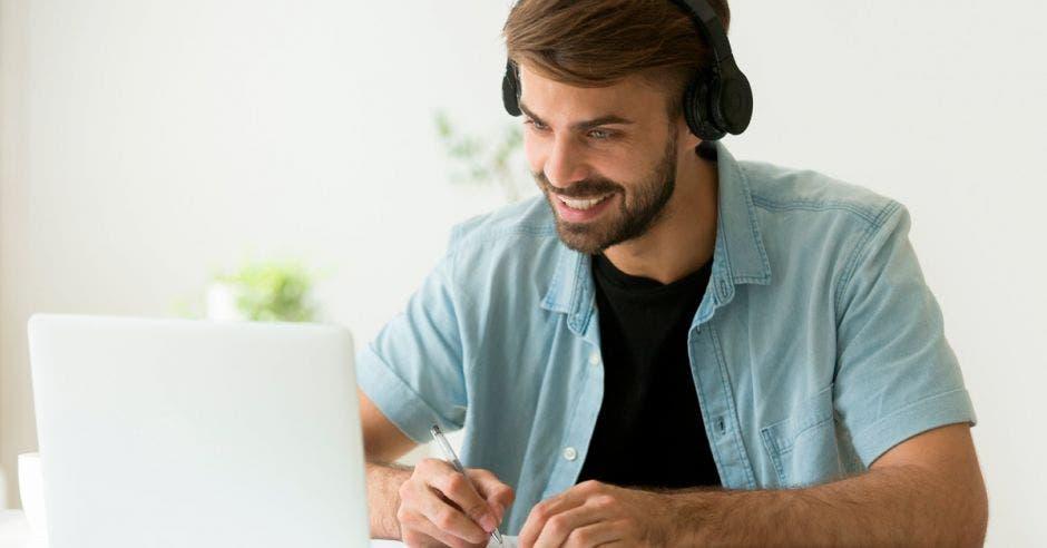 Un hombre de barba hace apuntes mientras mira su computadora