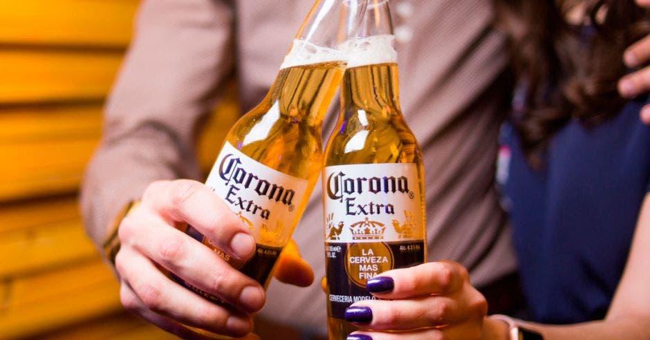 Dos jóvenes toman una cerveza marca corona