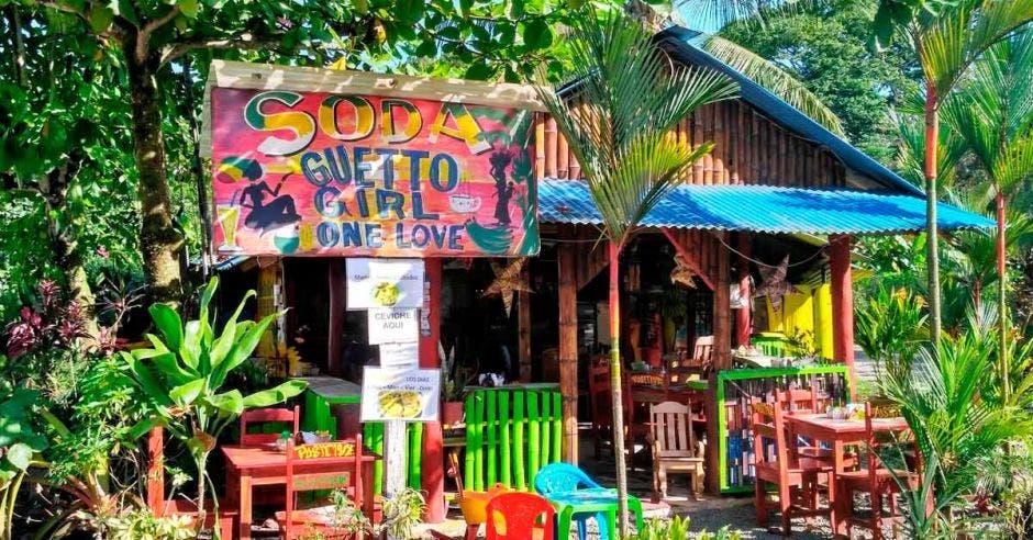 Restaurante tradicional costarricense Soda - colorida casa de madera rodeada de exuberante vegetación tropical en Puerto Viejo, Costa Rica