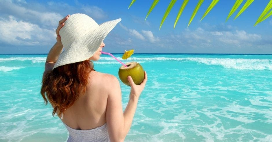 Una mujer toma con un coco con la playa de fondo