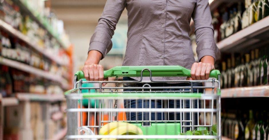 Una mujer empuja un carrito de supermercado