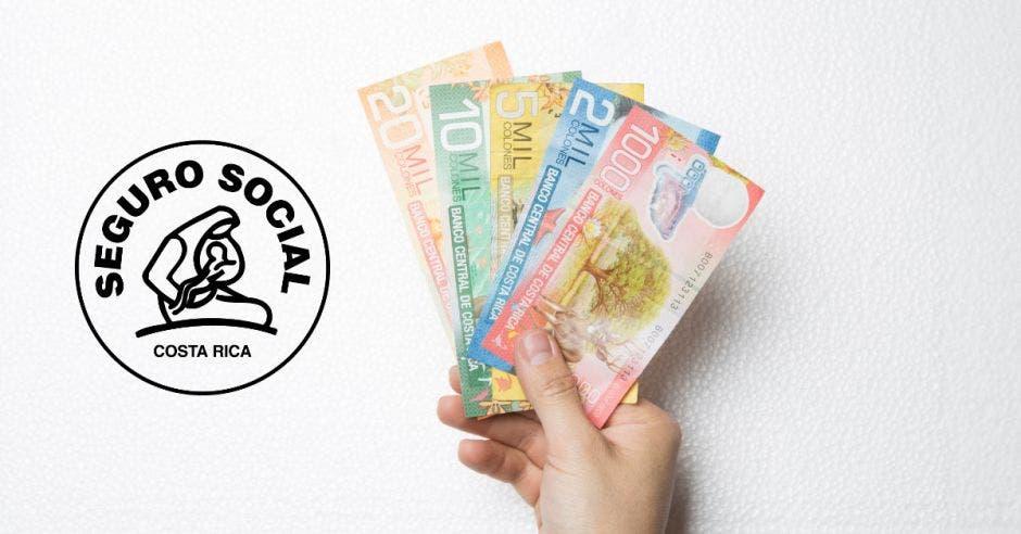 Una mano con billetes de Costa Rica y el logo de la Caja