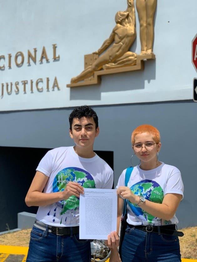 Dos jóvenes sostienen una hoja frente a la Sala Constitucional