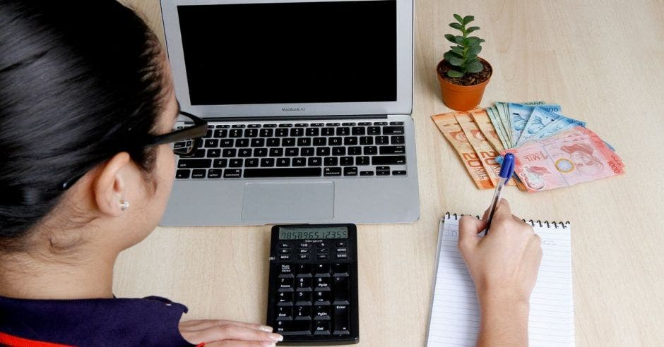 persona en escritorio  haciendo  cálculos