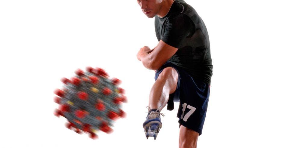 Un hombre pateando un balón en forma de una de las partículas que representan el Coronavirus