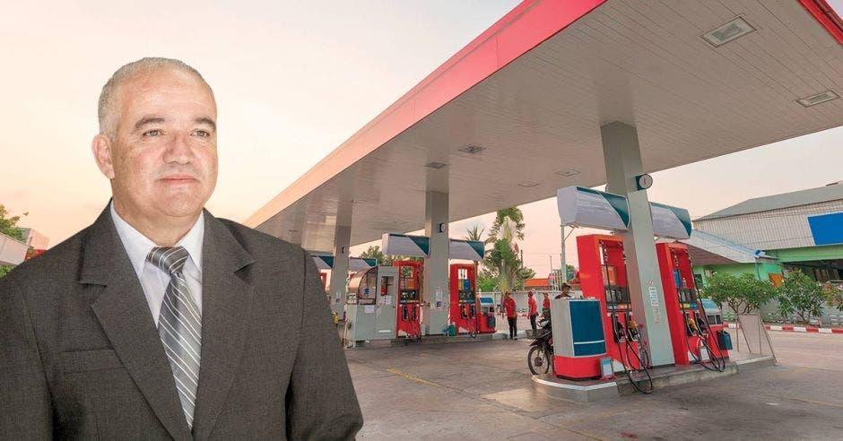 Un empresario con una gasolinera de fondo