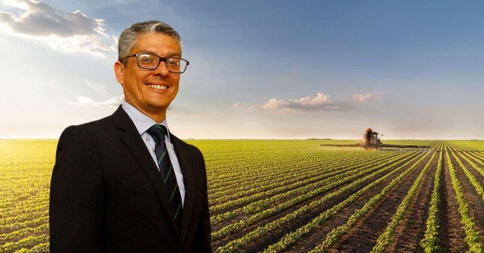 Un señor de mediana edad posa frente a un campo de agricultura