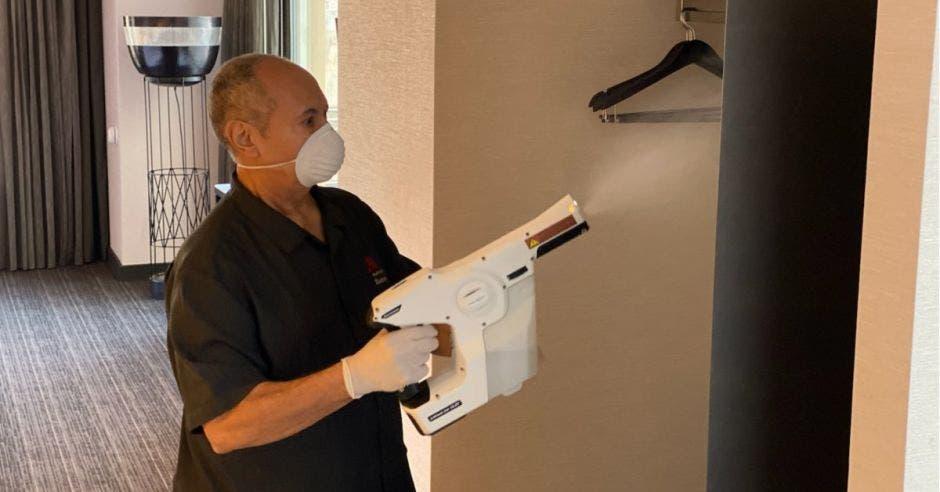 Hombre con pistola para desinfectar
