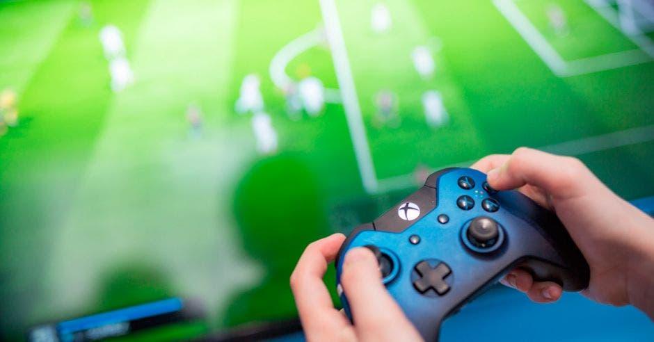 Un control de Xbox One, con una pantalla con un juego de fútbol