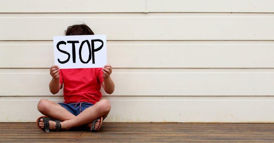 niño  con cartel de stop