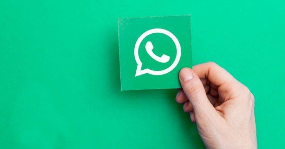 Una mano sosteniendo un ícono de WhatsApp