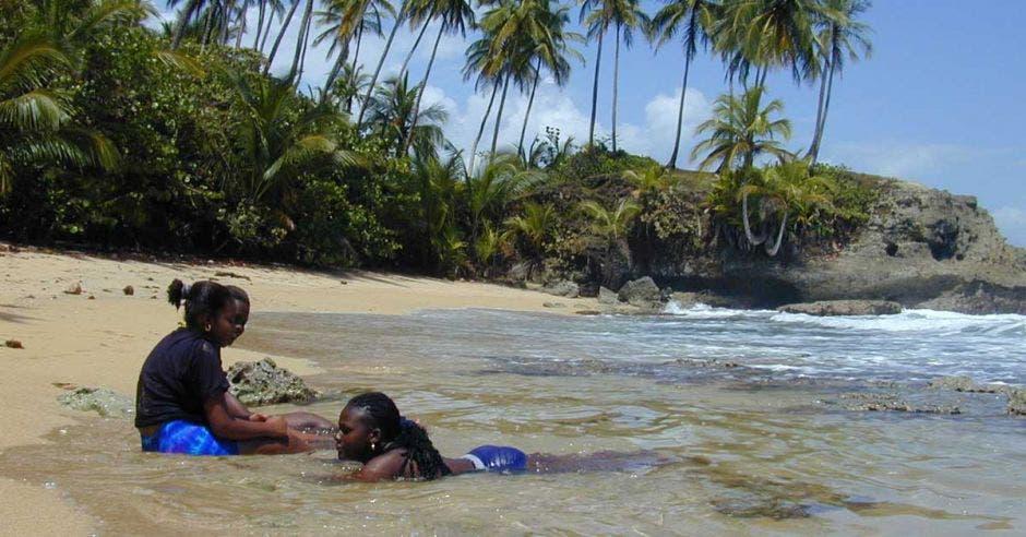 dos mujeres descansan en una playa limonense